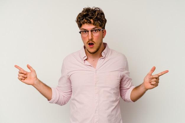 Junger kaukasischer mann isoliert auf weißem hintergrund, der auf verschiedene kopienräume zeigt, einen von ihnen auswählt und mit dem finger zeigt.