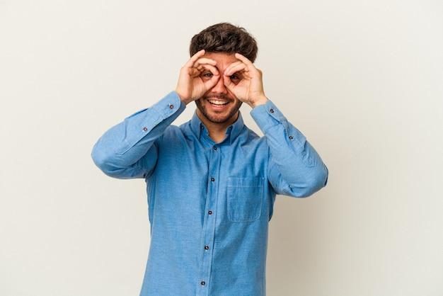 Junger kaukasischer mann isoliert auf weißem hintergrund, der ein okayzeichen über den augen zeigt