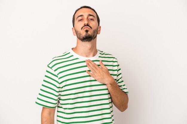 Junger kaukasischer mann isoliert auf weißem hintergrund, der einen eid leistet und die hand auf die brust legt.