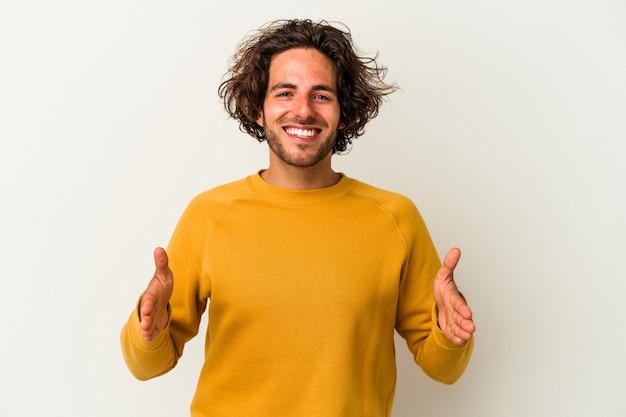 Junger kaukasischer mann isoliert auf weißem hintergrund, der etwas mit beiden händen hält, produktpräsentation.