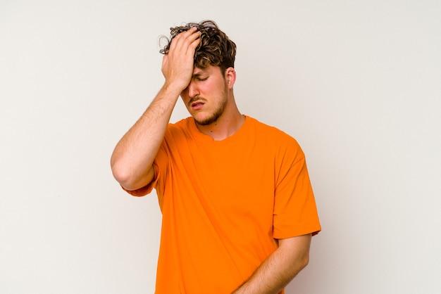 Junger kaukasischer mann isoliert auf weißem hintergrund, der etwas vergisst, mit der hand auf die stirn schlägt und die augen schließt.