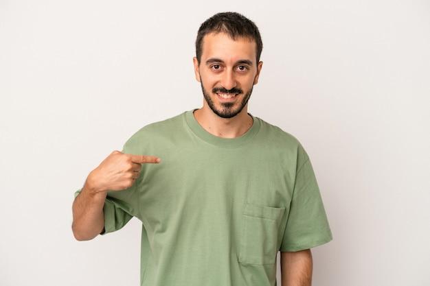Junger kaukasischer mann isoliert auf weißem hintergrund, der mit der hand auf einen hemdkopierraum zeigt, stolz und selbstbewusst