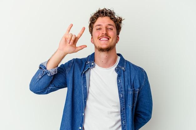 Junger kaukasischer mann isoliert auf weißem hintergrund, der rockgeste mit den fingern zeigt showing