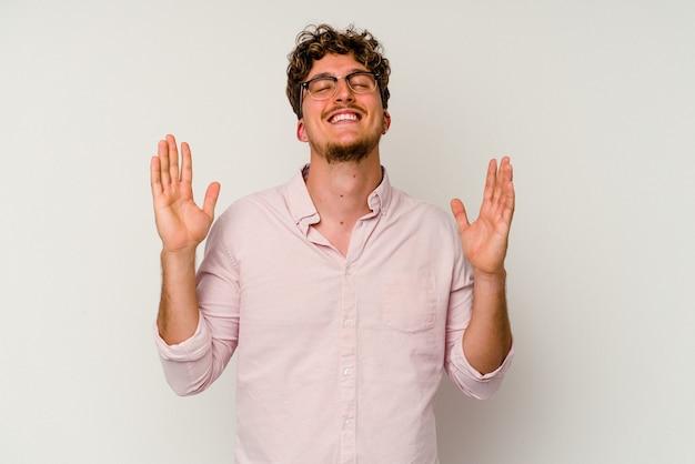 Junger kaukasischer mann isoliert auf weißem hintergrund lacht laut und hält die hand auf der brust.