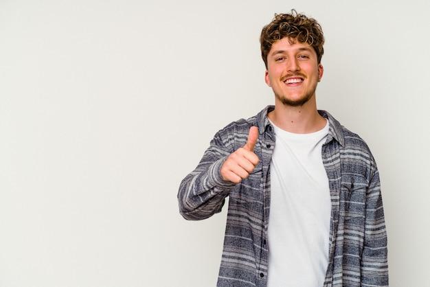 Junger kaukasischer mann isoliert auf weißem hintergrund lächelt und hebt daumen hoch