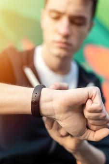Junger kaukasischer mann ist auf seinem fitnessarmband auf mehrfarbigem hintergrund