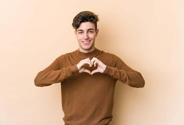 Junger kaukasischer mann lokalisiert auf beige lächelnd und zeigt eine herzform mit händen.