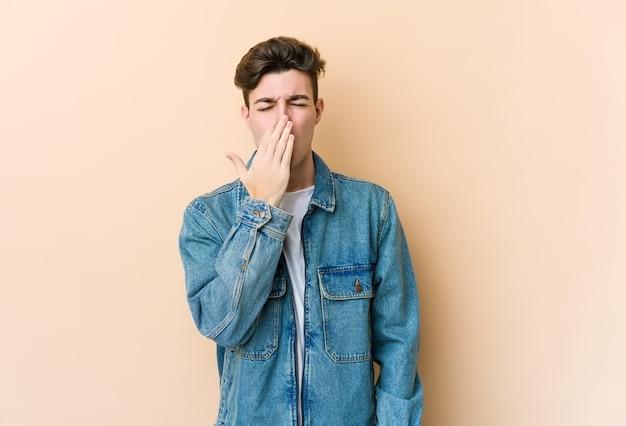 Junger kaukasischer mann lokalisiert auf beigem wandgähnen, der eine müde geste zeigt, die mund mit hand bedeckt.