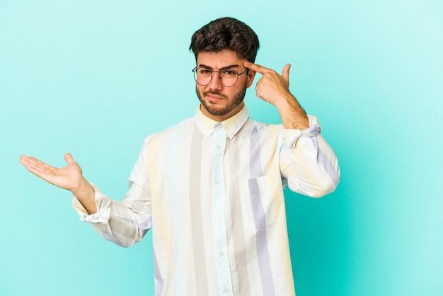 Junger kaukasischer mann lokalisiert auf blauem hintergrund, der ein produkt an hand hält und zeigt.
