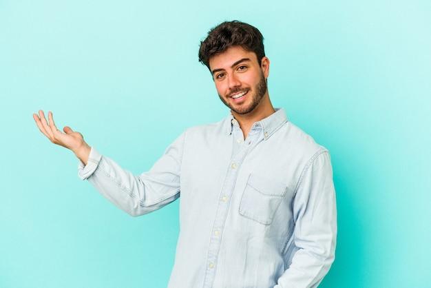 Junger kaukasischer mann lokalisiert auf blauem hintergrund, der einen willkommenen ausdruck zeigt.