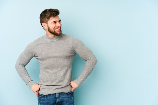 Junger kaukasischer mann lokalisiert auf blauem hintergrund lacht glücklich und hat spaß, hände auf bauch zu halten.