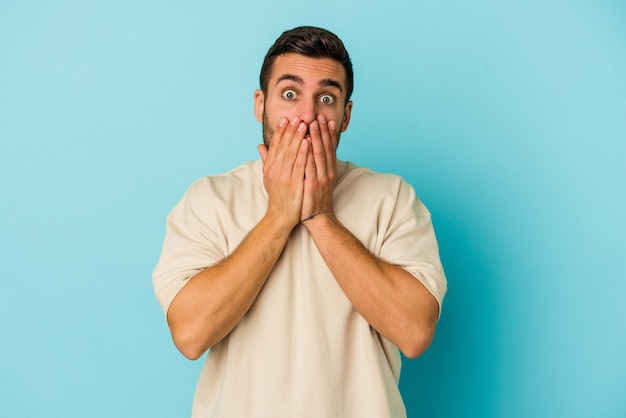 Junger kaukasischer mann lokalisiert auf blauem hintergrund schockiert, mund mit händen bedeckend, besorgt, etwas neues zu entdecken.