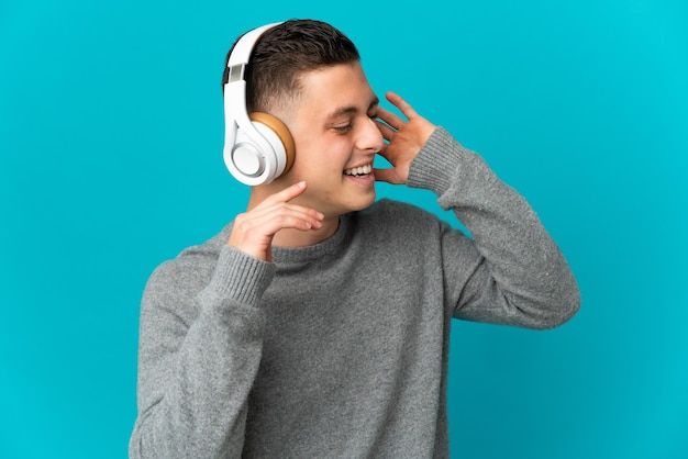Junger kaukasischer mann lokalisiert auf blauer wand, die musik hört und singt