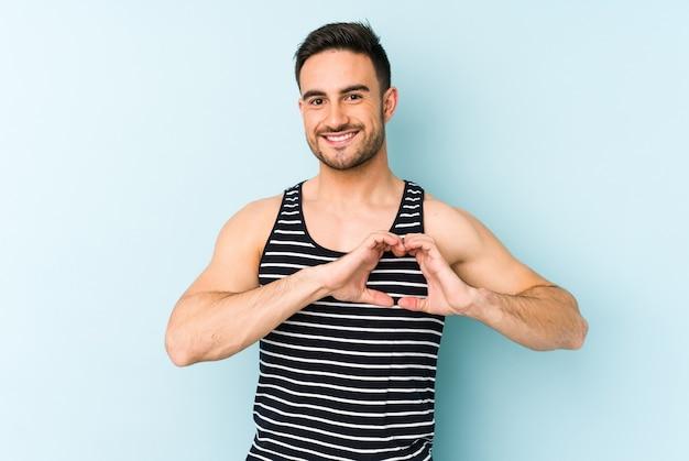 Junger kaukasischer mann lokalisiert auf blauer wand lächelnd und zeigt eine herzform mit händen.