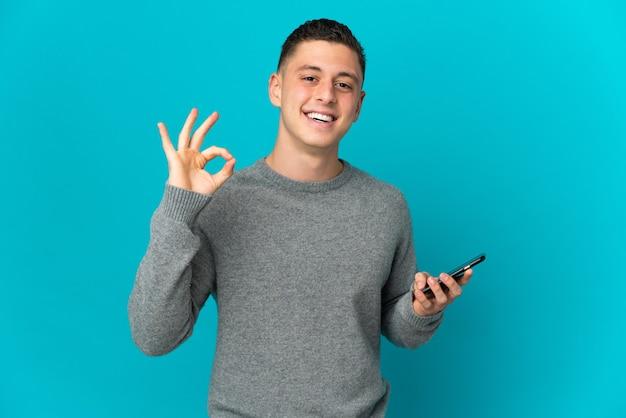 Junger kaukasischer mann lokalisiert auf blauer wand unter verwendung des handys und des ok-zeichens