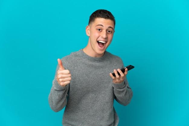 Junger kaukasischer mann lokalisiert auf blauer wand unter verwendung des mobiltelefons, während daumen hoch