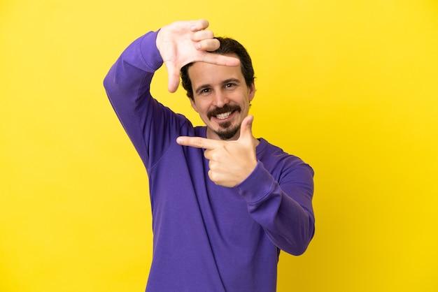 Junger kaukasischer mann lokalisiert auf dem fokusgesicht des gelben hintergrundes. rahmensymbol