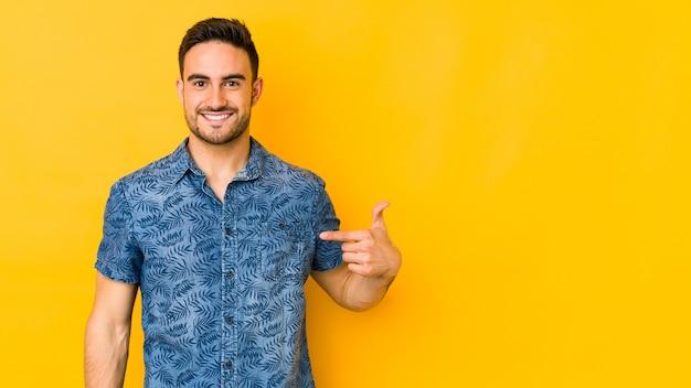 Junger kaukasischer mann lokalisiert auf gelbe person, die von hand auf einen hemdkopierraum zeigt, stolz und zuversichtlich