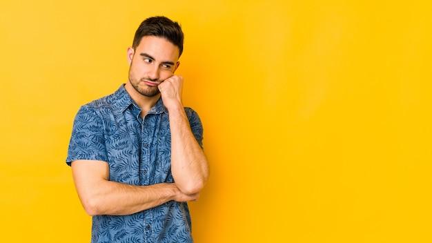 Junger kaukasischer mann lokalisiert auf gelbem backgrund, der sich traurig und nachdenklich fühlt und kopierraum betrachtet.