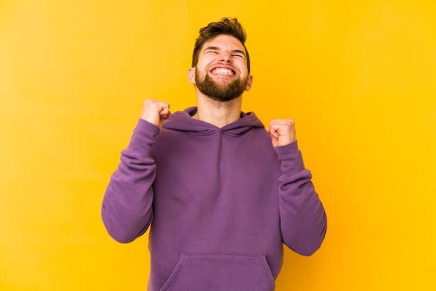 Junger kaukasischer mann lokalisiert auf gelbem hintergrund, der einen sieg, eine leidenschaft und einen onthusiasmus, glücklichen ausdruck feiert.