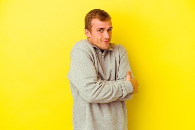 Junger kaukasischer mann lokalisiert auf gelben umarmungen, sorglos lächelnd und glücklich.