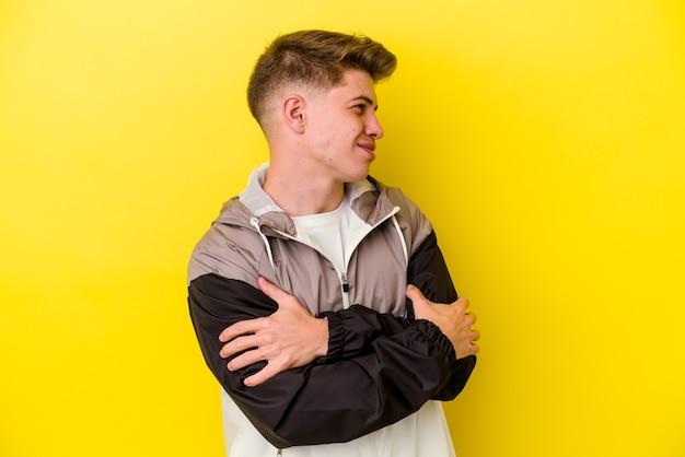 Junger kaukasischer mann lokalisiert auf gelben wandumarmungen, lächelnd sorglos und glücklich.