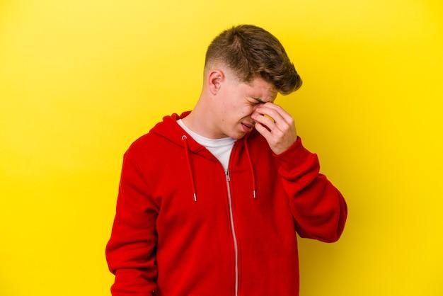 Junger kaukasischer mann lokalisiert auf gelber wand, die einen kopfschmerz hat, der vorderseite des gesichts berührt.