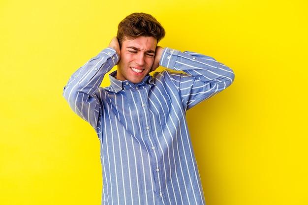 Junger kaukasischer mann lokalisiert auf gelber wand, die ohren mit händen bedeckt