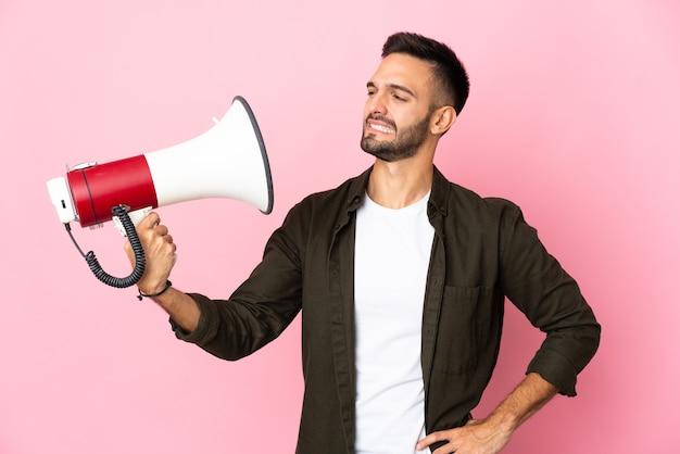 Junger kaukasischer mann lokalisiert auf rosa hintergrund, der ein megaphon mit gestresstem ausdruck hält