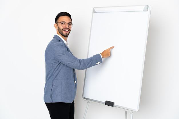 Junger kaukasischer mann lokalisiert auf weißem hintergrund, der eine präsentation auf weißer tafel gibt und darin schreibt