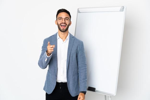 Junger kaukasischer mann lokalisiert auf weißem hintergrund, der eine präsentation auf weißer tafel gibt und überrascht ist, während er nach vorne zeigt