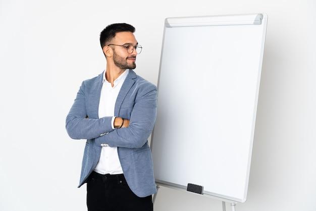 Junger kaukasischer mann lokalisiert auf weißem hintergrund, der eine präsentation auf weißer tafel gibt und zweifel gestikuliert