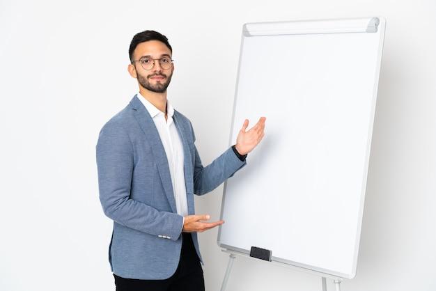 Junger kaukasischer mann lokalisiert auf weißem hintergrund, der eine präsentation auf weißer tafel gibt