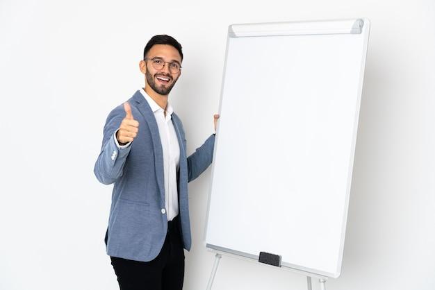 Junger kaukasischer mann lokalisiert auf weißem hintergrund, der eine präsentation auf weißer tafel mit daumen oben gibt