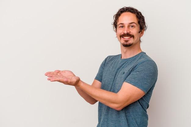 Junger kaukasischer mann lokalisiert auf weißem hintergrund, der einen kopienraum auf einer handfläche hält.