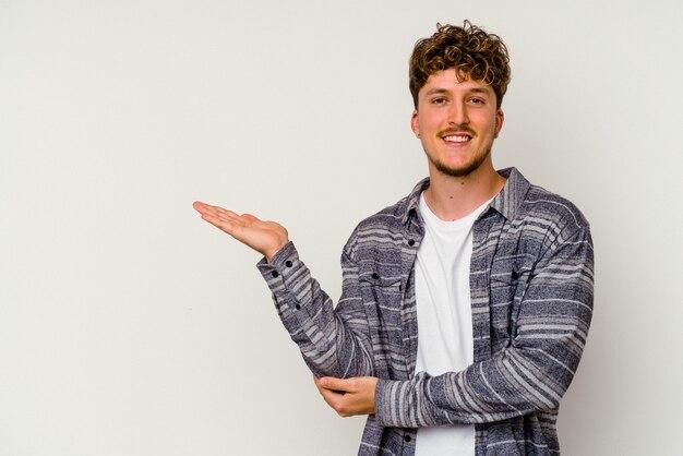 Junger kaukasischer mann lokalisiert auf weißem hintergrund, der einen kopienraum auf einer palme zeigt und eine andere hand auf taille hält.