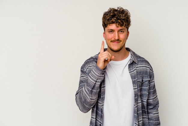 Junger kaukasischer mann lokalisiert auf weißem hintergrund, der nummer eins mit finger zeigt.