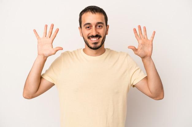 Junger kaukasischer mann lokalisiert auf weißem hintergrund, der nummer zehn mit den händen zeigt.