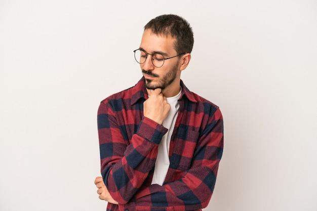Junger kaukasischer mann lokalisiert auf weißem hintergrund, der seitlich mit zweifelhaftem und skeptischem ausdruck schaut.