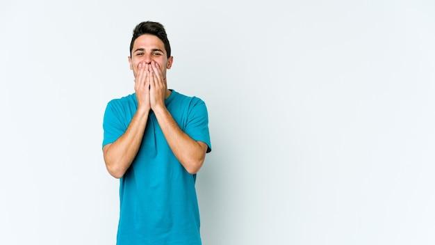 Junger kaukasischer mann lokalisiert auf weißem hintergrund, der über etwas lacht und mund mit händen bedeckt.