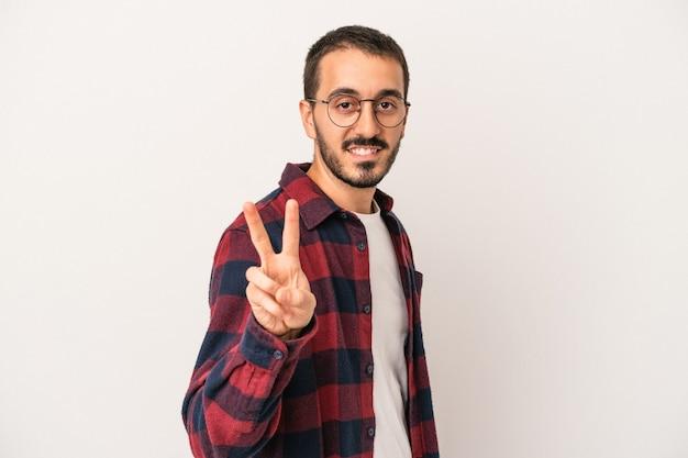 Junger kaukasischer mann lokalisiert auf weißem hintergrund, der victory-zeichen zeigt und breit lächelt.