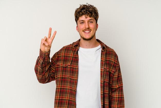 Junger kaukasischer mann lokalisiert auf weißem hintergrund freudig und unbeschwert, der ein friedenssymbol mit den fingern zeigt.