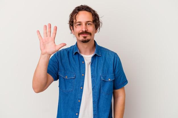 Junger kaukasischer mann lokalisiert auf weißem hintergrund lächelnd fröhlich zeigt nummer fünf mit den fingern.
