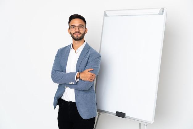 Junger kaukasischer mann lokalisiert auf weißem hintergrund mit verschränkten armen beim geben einer präsentation auf weißer tafel