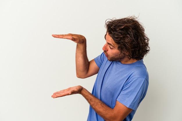 Junger kaukasischer mann lokalisiert auf weißem hintergrund schockiert und überrascht, einen kopienraum zwischen den händen zu halten.