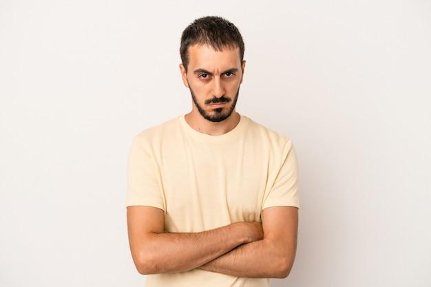 Junger kaukasischer mann lokalisiert auf weißem hintergrund unglücklich, der mit sarkastischem ausdruck in die kamera schaut.