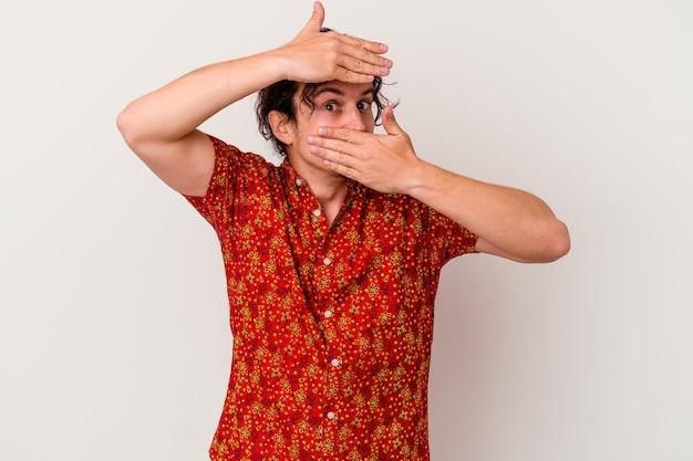 Junger kaukasischer mann lokalisiert auf weißer wand blinken durch finger, verlegenes bedeckendes gesicht.