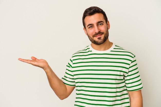 Junger kaukasischer mann lokalisiert auf weißer wand, die einen kopienraum auf einer handfläche zeigt und eine andere hand auf taille hält.