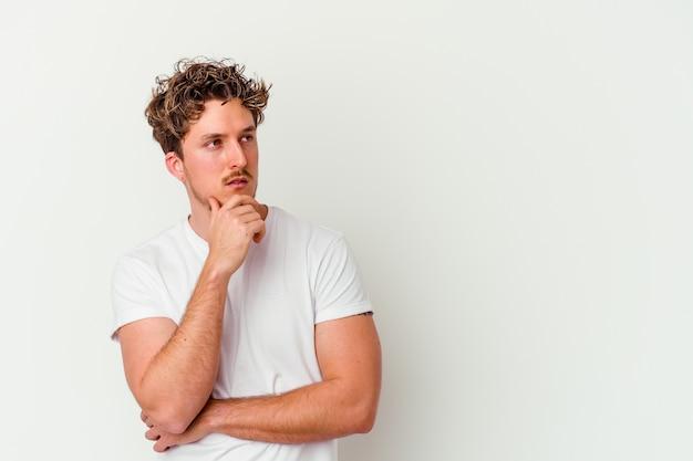 Junger kaukasischer mann lokalisiert auf weißer wand, die seitwärts mit zweifelhaftem und skeptischem ausdruck schaut.