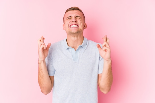 Junger kaukasischer mann lokalisierte überfahrtfinger für das haben des glücks